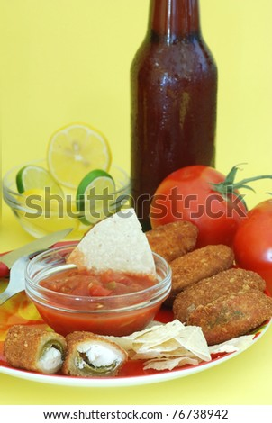 Jalapeno poppers on red plate with chips and salsa and surrounded by Mexican food ingredients; served with ice-cold beer on yellow background and party atmosphere.