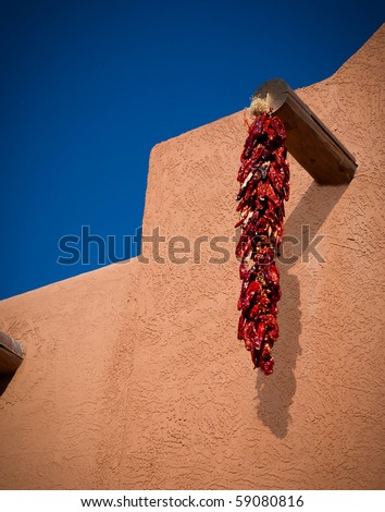 Jalapeno red chilies hang to dry by pueblo in New Mexico
