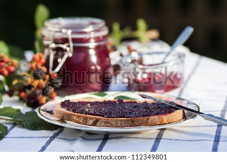 jam bread on a plate with homemade blackberry jam and blackberries in the background