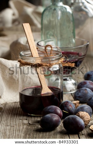 Jam in jar and fresh plums on old wooden table