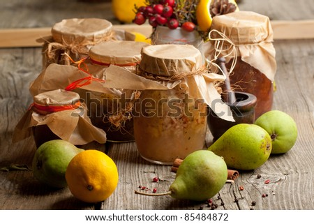 Jam in jars and fresh pears and lemon on old wooden table