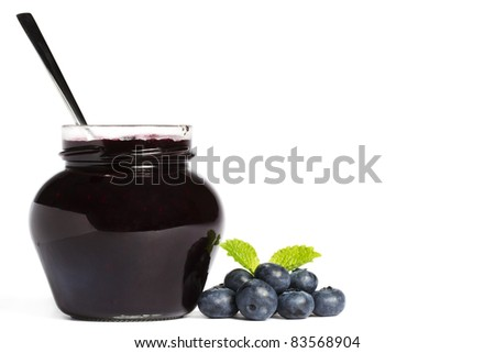 jam jar with blueberry jam a spoon and blueberries with a leaf melissa aside on white background