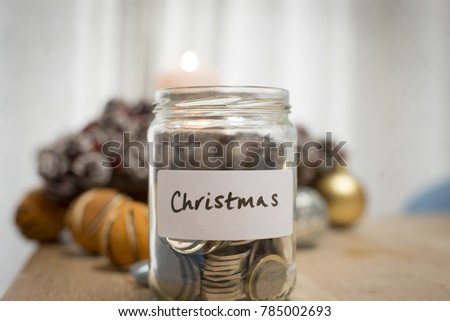 Jam jar with coins to illustrate saving for Christmas to illustrate saving for Christmas #785002693