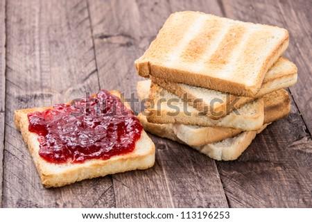 Jam on toast on wooden background