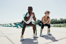 Jamaican man in white t-shirt and black shorts with elastic tape doing squats with women in grey top and black pants on fresh air and sunny weather.