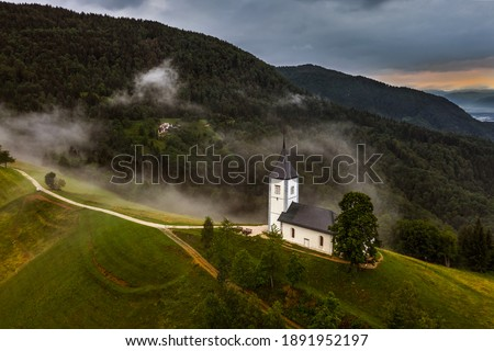 Jamnik, Slovenia - Aerial drone view of a foggy summer sunrise at Jamnik St.Primoz church. The fog gently goes around the small chapel with colorful sky and Julian Alps at background  Zdjęcia stock ©