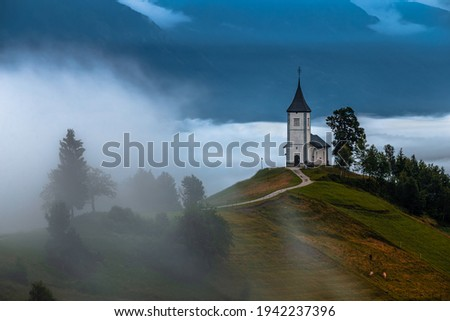 Jamnik, Slovenia - Foggy summer morning at Jamnik St.Primoz hilltop church. The fog gently goes around the small hilltop chapel with green fields and animals on the top of the hill Zdjęcia stock ©