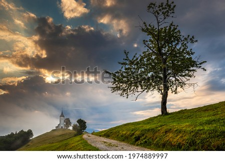 Jamnik, Slovenia - Magical foggy summer morning at Jamnik St.Primoz church with small gravel road and tree. The fog goes around the small chapel with blue sky and rising sun at background Zdjęcia stock ©