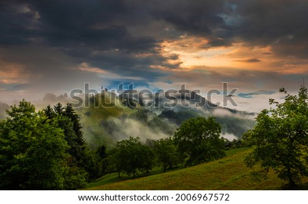 Jamnik, Slovenia - Magical foggy summer sunrise at Jamnik St.Primoz church. The fog gently goes by the small chapel with colorful sky and Julian Alps at background  Zdjęcia stock ©