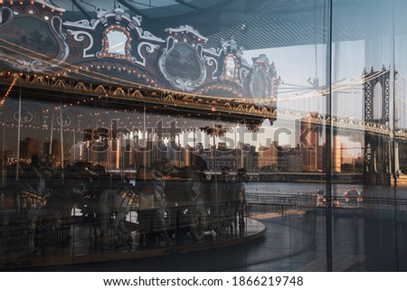 Photo of  Jane's Carousel and the Manhattan bridge reflected on glass at Brooklyn Bridge Park on September 20, 2013 in New York, USA.