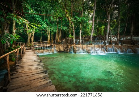 Jangle landscape tropical rain forest landscape with wooden bridge with amazing turquoise water of Kuang Si cascade waterfall at tropical rain forest near Luang Prabang, Laos