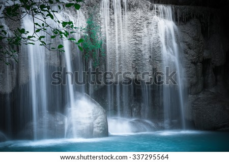Jangle landscape with flowing turquoise water of Erawan cascade waterfall at deep tropical rain forest. National Park Kanchanaburi, Thailand stock photo