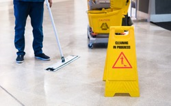 Janitor Cleaning Floor In Front Of Yellow Caution