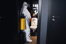 Janitor in a hazmat suit sanitizing the public lavatory