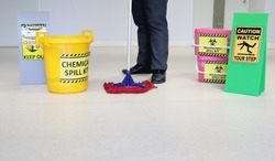 Janitor male cleaning floor in medical service room or laboratory with caution tag sign watch your step and Biohazard spill kit, chemical spill kit yellow bucket for response chemical spill out cases.