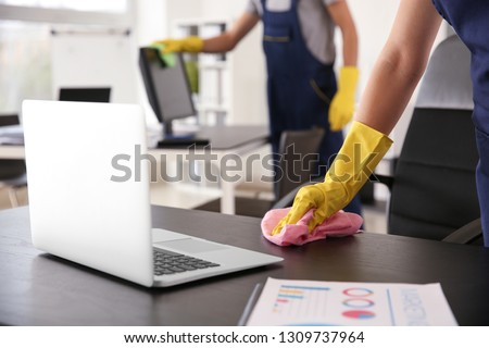 Janitor wiping table in office Stock photo ©