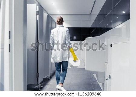 Janitor woman changing paper in public toilet or restroom