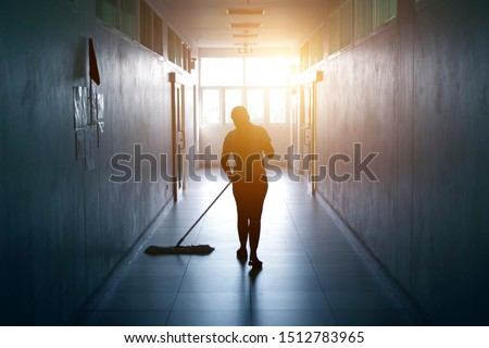 Janitor woman mopping floor in hallway office building or walkway after school and classroom silhouette work job with sun light background. Poor people working job.