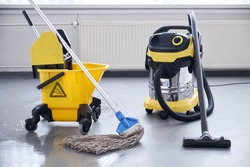 Janitorial service. Mop and bucket with professional vacum cleaner.