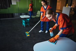 Janitorial workforce in uniforms tidying up the cafe