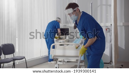 Janitors in scrubs and safety mask cleaning hospital room. Medical staff in protective wear wiping floor and changing bedsheets in empty ward in clinic
