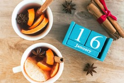 January 16. Blue cube calendar with month and date and cups with mulled wine, wooden background.