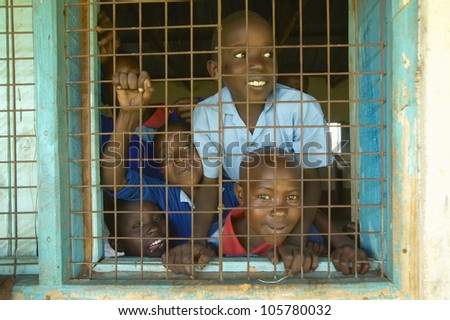 JANUARY 2005 - Children in blue uniforms in window at school near Tsavo National Park, Kenya, Africa