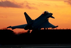 January 2012. Eurofighter Typhoon supersonic fighter aircraft unmarked but flying with No 29[R] Squadron. RAF Coningsby, Lincolnshire, UK. Seen landing at sunset. Silhouette.