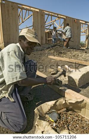 JANUARY 2007 - Man helps construct new houses for Pepo La Tumaini Jangwani, HIV/AIDS Community Rehabilitation Program, Orphanage & Clinic. Nairobi, Kenya, Africa