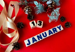 January 13 on wooden cubes.Near fir branches, cones, ribbon, gift box on a red background.Beginning of year .Calendar for January
