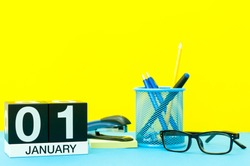 January 1st. Day 1 of january month, calendar on yellow background with office supplies. Winter time