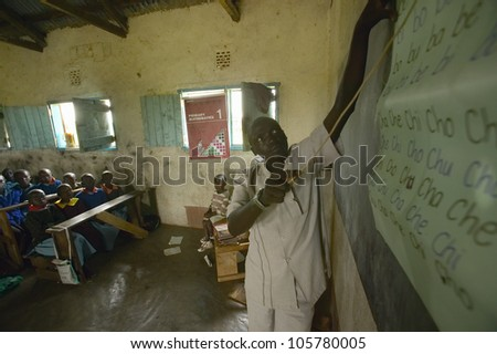 JANUARY 2005 - Teacher of English syllables to children in blue uniforms at school behind desk near Tsavo National Park, Kenya, Africa