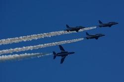 Japan Air Self Defense Force aerobatic team Blue Impulse flying in deep blue sky