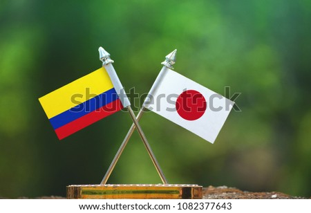 Japan and Colombia small flag with blur green background #1082377643