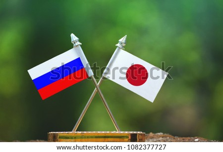 Japan and Russia small flag with blur green background #1082377727