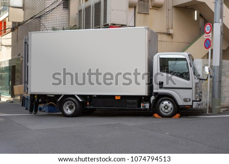 Japan Cargo truck with a blank container for Mockup parking in front of building background