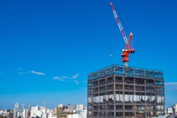 Japan. Construction in Kyoto. A crane is building a building in Japan. The construction of skyscrapers in the Japanese city. Construction crane while working on blue sky background. Cities of Japan