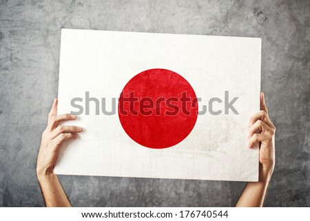 Japan flag. Man holding banner with Japanese Flag. Supporting national team, patriotism concept.