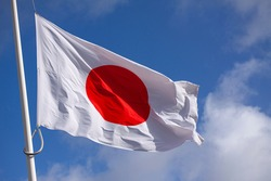 Japan flag waving in the wind against blue sky. Close up image.