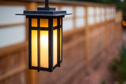 Japan hanging lantern lamp in Japanese garden with house temple wall blurry bokeh background and illuminated light in evening night