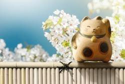 Japan Maneki Neko or Beckoning Cat standing on Bamboo Fence over Japanese Blossom Sakura Flower. Mascot of Lucky, Fortune and Money