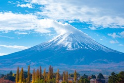 Japan. Mount Fuji. Snow on top of volcano Fujiyama. Clouds cover the top of Mount Fujiyama. Landscapes of Japan. Mount Fuji in the background of blue sky with clouds. Natural attractions of Japan