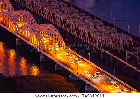 Japan. Road bridge in Osaka. Bridges over the Yodo River at night. Cars ride over the bridge top view. Night lights on the japanese bridge. Osaka city road architecture. Traveling in Japan by car.