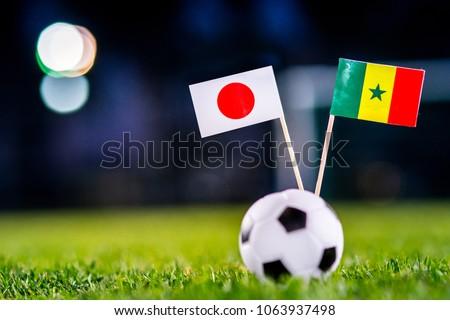 Japan - Senegal, Group H, Sunday, 24. June, Football, National Flags on green grass, white football ball on ground. #1063937498
