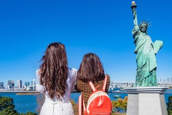 Japan. Statue of liberty on Odaiba island. Two girls look at the Statue of Liberty in Tokyo. Attractions of the Japanese capital. Women and a statue against the blue sky. Monuments Of Tokyo.