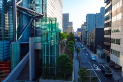 Japan. Tokyo. Tokyo street in the afternoon. Glass Elevator shaft at the office building. Elevator with glass walls. The business part of Tokyo. Japanese city street in the afternoon.