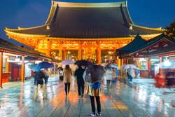 Japan. Tourists near the temple of Asakusa. People with umbrellas on the background of the Japanese temple. Sensoji during the evening rain. People walk the streets of Tokyo. Man admires the temple