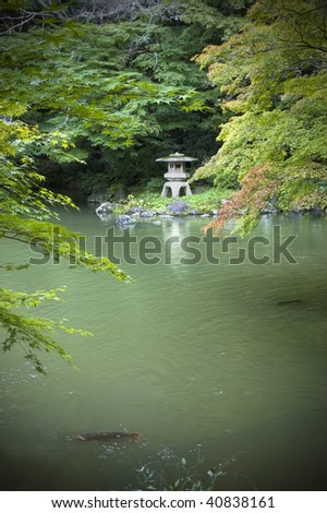 Japanede garden with Koi pond,carps and lantern. Vertical shot.