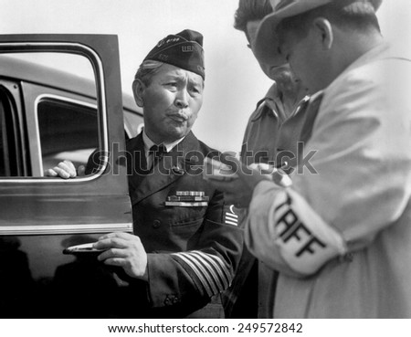 Japanese-American veteran, dressed in his WW2 uniform, reports for his WW2 internment. Santa Anita Park assembly, Arcadia, California, April 5, 1942. Photo by Dorothea Lange.