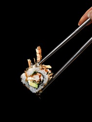 Japanese and Asian cuisine sushi rollin Chinese chopsticks with fresh ingredients over black background with text copy space